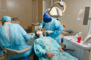 dentists performing oral surgery on a patient