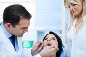 dentist determining if patient needs dental fillings or dental sealants